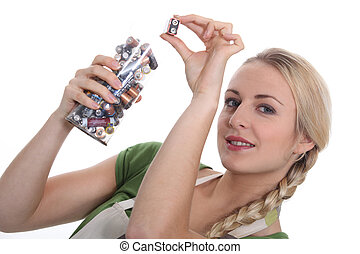 a blonde woman collecting batteries for recycling