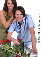 Couple with trolley full of vegetables