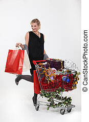 Woman standing by trolley full of Christmas gifts