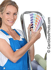 A woman wearing dungarees and showing us a range of colors.