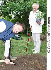 Senior with gardener digging border