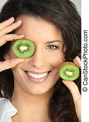 Woman covering eye with kiwi