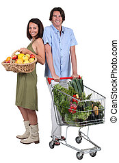 Market vs supermarket: Couple shopping for fruit and...