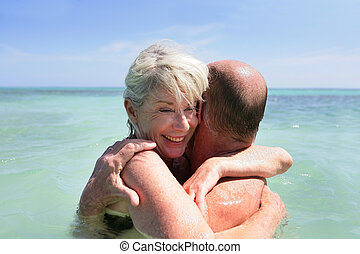 Older couple embracing in the sea