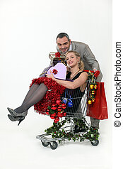 Couple with trolley full of Christmas gifts