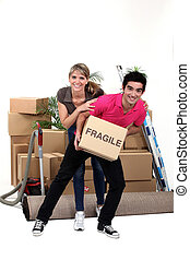 Playful couple moving house