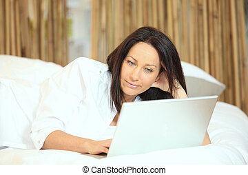 Woman with a laptop on her bed