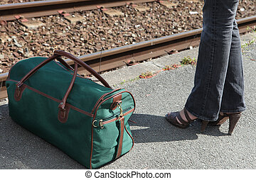 Woman in jeans with a bag on a railway platform