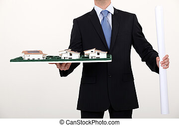 businessman holding an architectural model and a blueprint