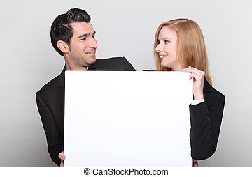 Man and woman smiling with panel in hand