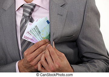 Businessman pulling money out of pocket