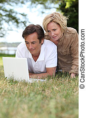 Couple using their laptop in a public park