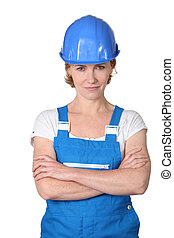 Woman wearing blue work overalls and hard hat
