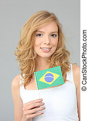 a blonde woman showing a Brazilian flag