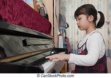 Asian kid playing piano - Asian kid learning to play piano...