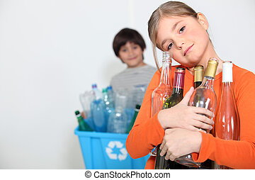 A girl and a boy recycling glass bottles