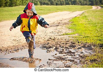 Boy splashing in puddle, having fun