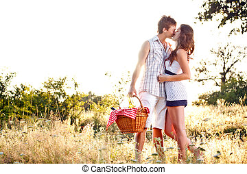 Young romantic couple kissing on their way to a picnic