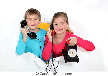 Brother and sister with old-fashioned telephone