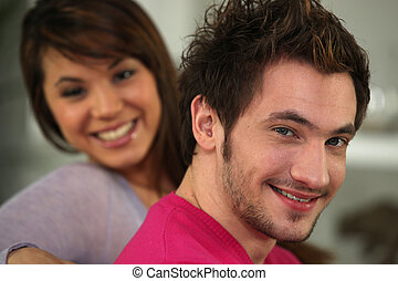 Profile shot of young couple relaxing on their sofa