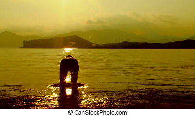 Man diving in the sea at sunset