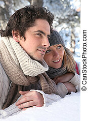Attractive couple laying in the snow