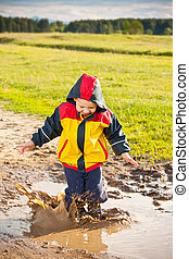 Little boy jumping in a mud puddle