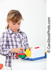 Young girl playing with a toy till