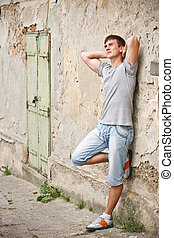 Young man leaning on a grunge wall