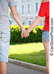 Young couple holding hands - Mid section image of a young...