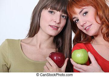 Girls holding apples