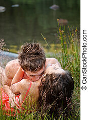 Young couple on the shore - Young couple kissing on the...