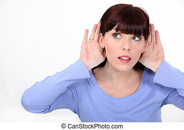 Woman with her hands to her ears listening