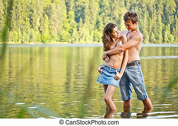 Young couple flirting on a montain lake