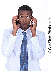 African businessman holding two telephones