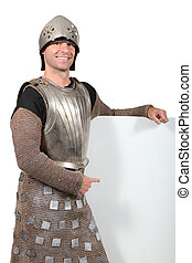 Man in knight's costume pointing at board blank for your message