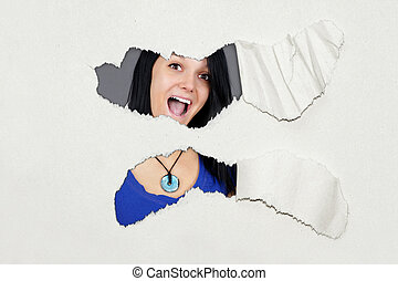 Surprised young woman under ripped paper