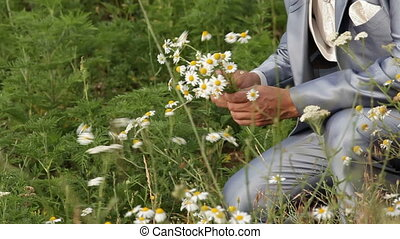 Picking flowers - Groom picking daisies in the field