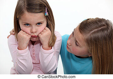 A little girl trying to cheer up her sister.
