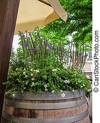 Old wooden barrel with flowers - Old wooden wine or beer...
