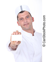 Chef holding up a blank business card