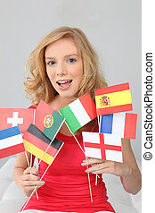 Fair haired woman with a variety of European flags
