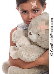 Girl and teddy with a plaster on forehead