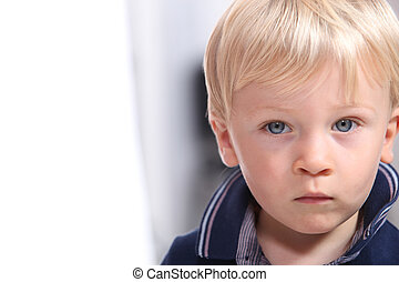 Landscape portrait of a serious little boy with blonde hair...