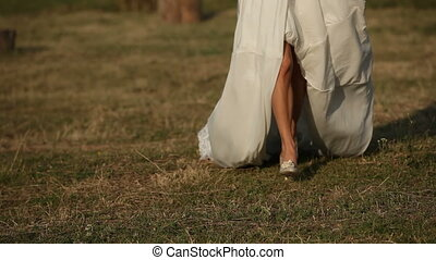 Bride running across the field - Close up on the legs of a...