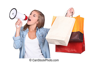 Studio shot of woman shouting into a megaphone and holding...