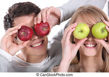 Man and woman covering her eyes with apples