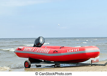 Rubber lifeguard boat trailer on sea shore - Rubber...
