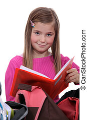 Schoolgirl removing book from backpack