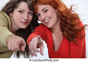 Two attractive women pointing fingers